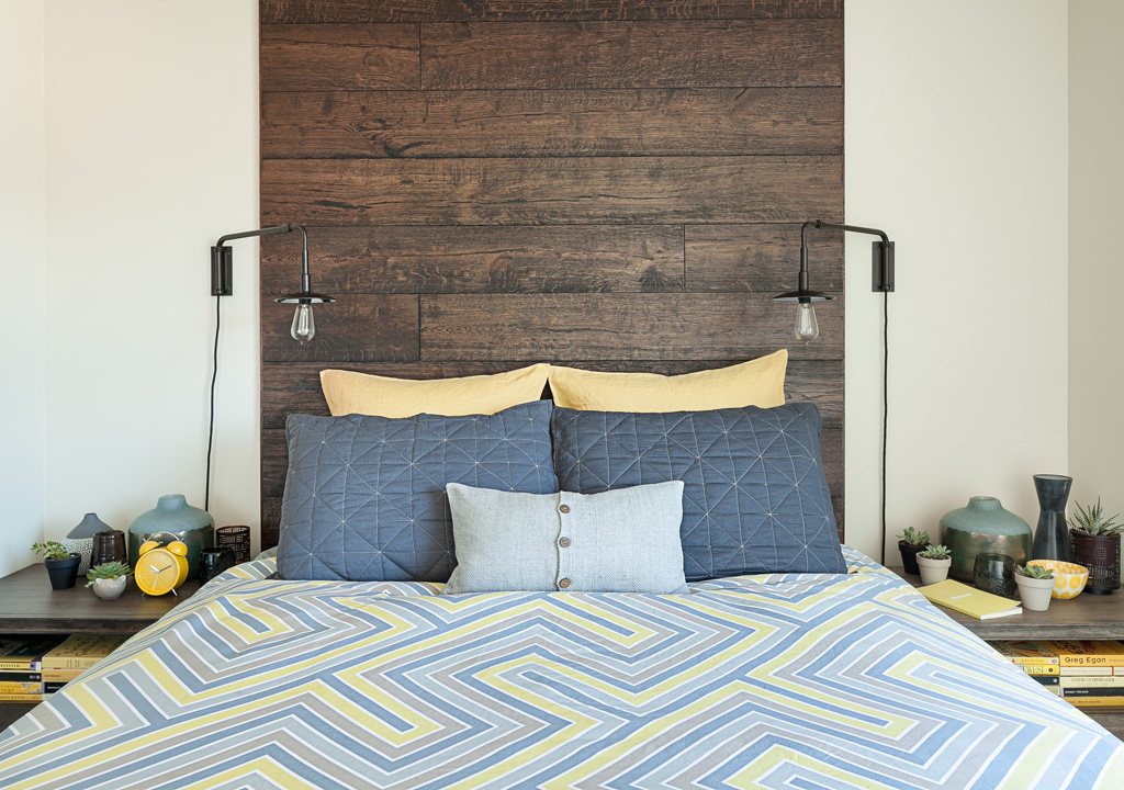 a bed with a dark wood headboard and yellow accents