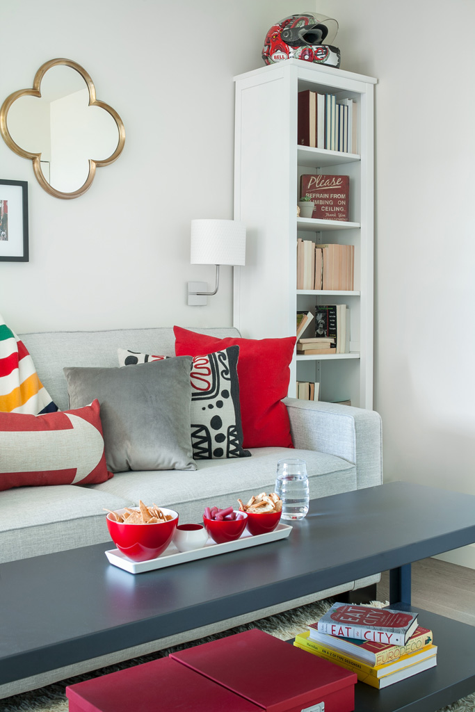 den with grey sofa and red accents