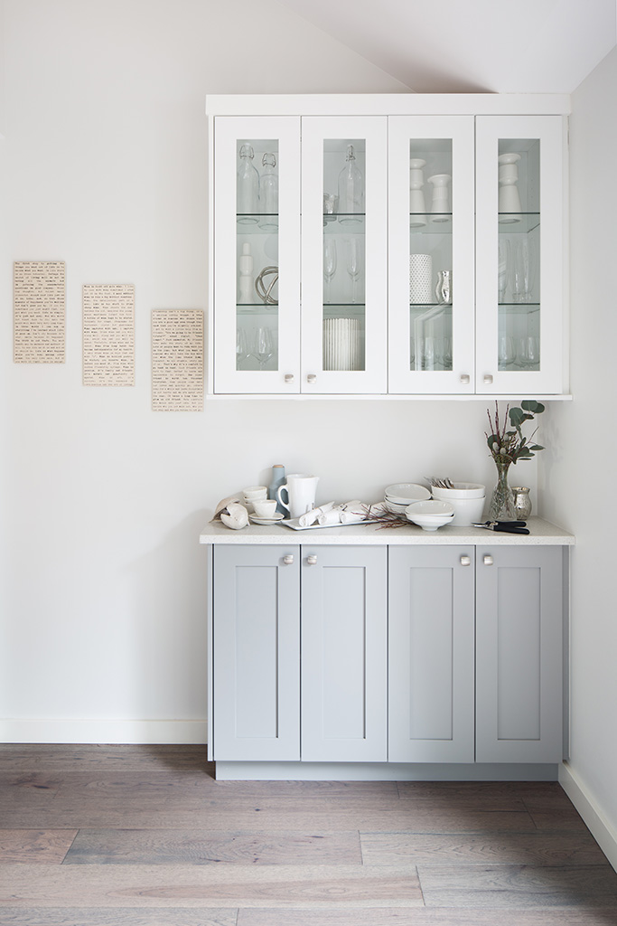 a grey sideboard and a white glass-fronted cabinet, ready to set the table