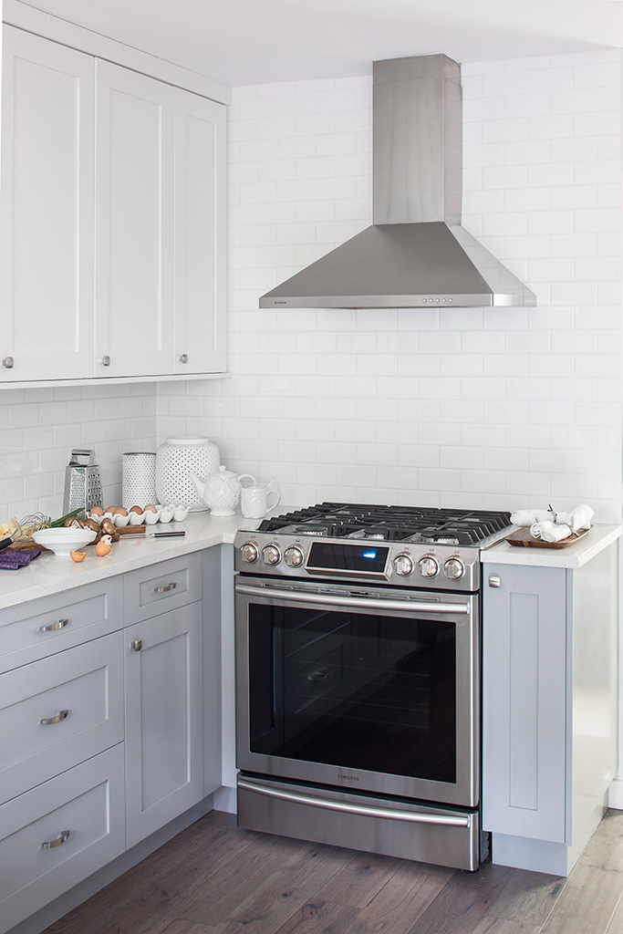 a mostly white kitchen with a stainless steel range and eggs out on the counter