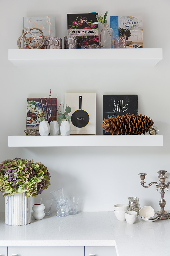 three floating shelves with cookbooks and decorative objects