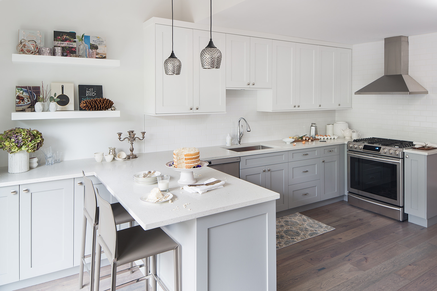 a photo of a white and grey kitchen with a layer cake on the counter