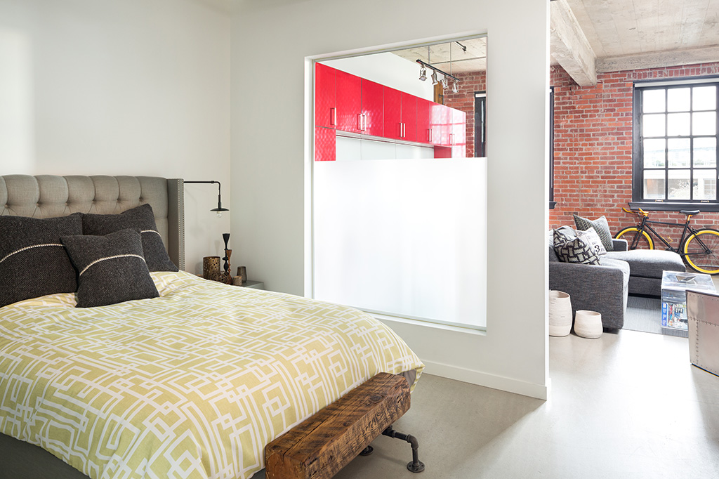 the view from the foot of a bed with a yellow geometric duvet into a living room with exposed brick
