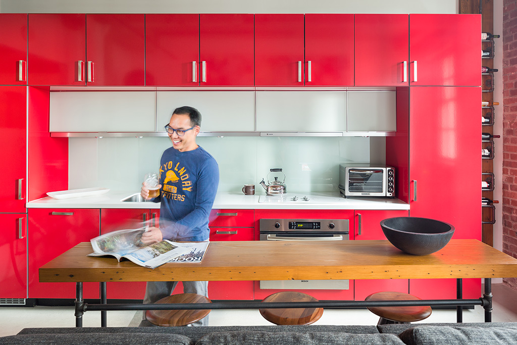 a man in a kitchen with modern red cabinetry