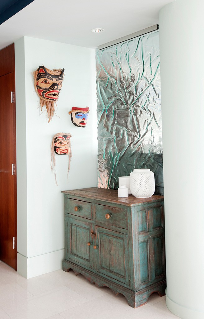 a hutch with three First Nations masks on the wall above.