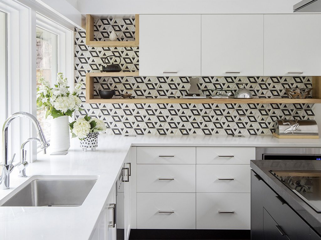 White kitchen with wood accents and black and white tile wall.