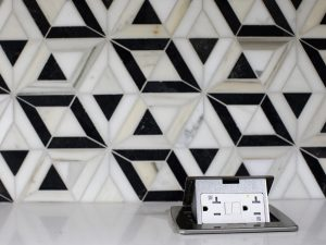 Detail of hidden countertop outlets with black and white tile wall in the background.