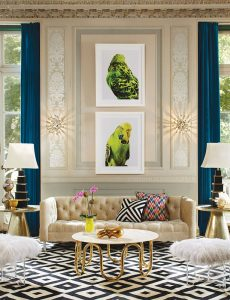 An eclectic living room with millwork on the walls, and two large artworks featuring a lime green budgie