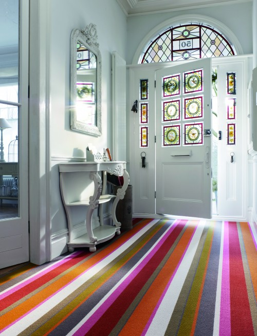 A hall runner carpet in bold stripes of warm colours