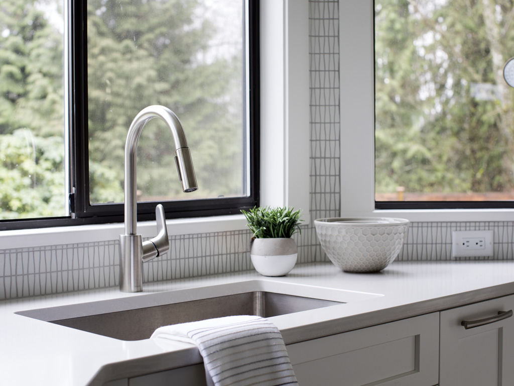 The sink area of a modern white kitchen