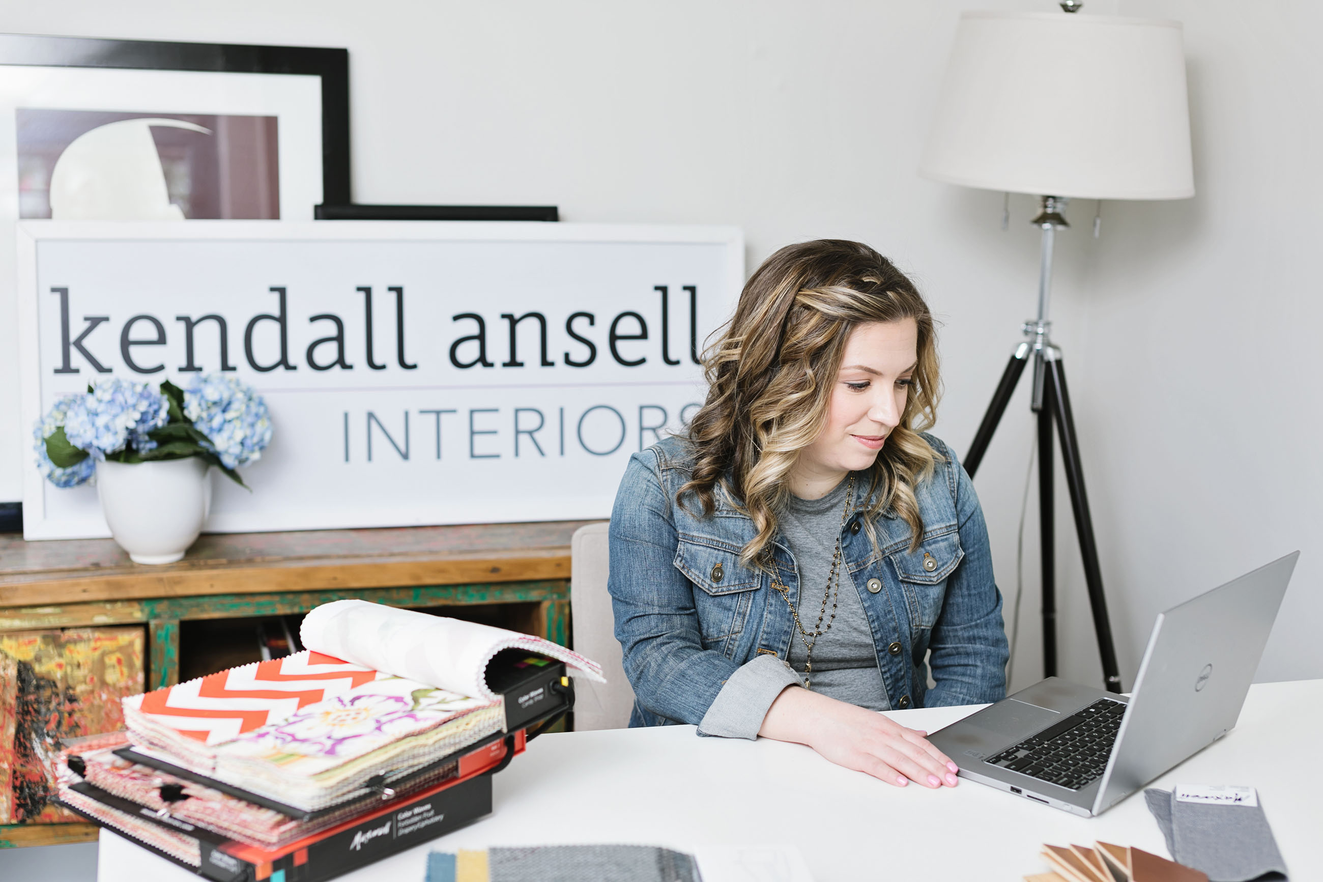 Kendall Ansell at her desk, surrounded by swatch books.